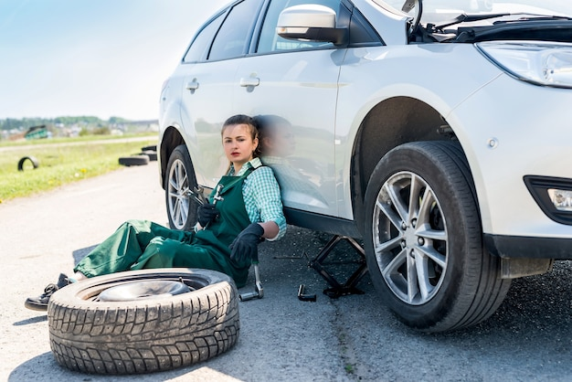 Tired mechanic with spare wheel and different tools