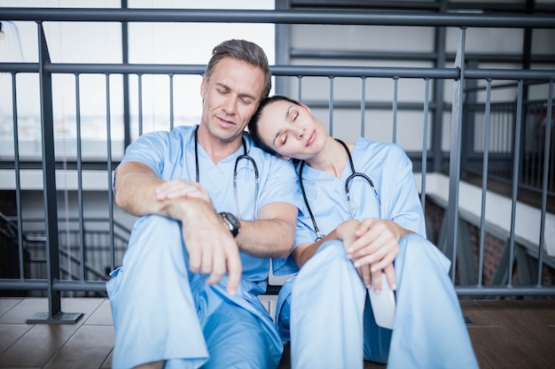 Tired medical team falling asleep on floor at hospital