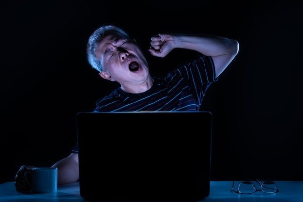 Tired middle age asian male yawning while working on his computer in his home office at night