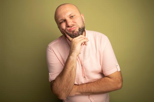 Uomo calvo di mezza età stanco che indossa la maglietta rosa che mette la mano sotto il mento