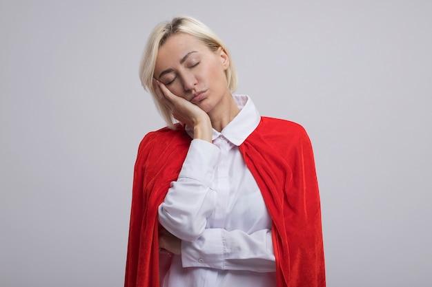 빨간 망토를 입은 피곤한 중년 금발 슈퍼히어로 여성이 카피 공간이 있는 흰 벽에 격리된 닫힌 눈으로 얼굴에 손을 대고 있다