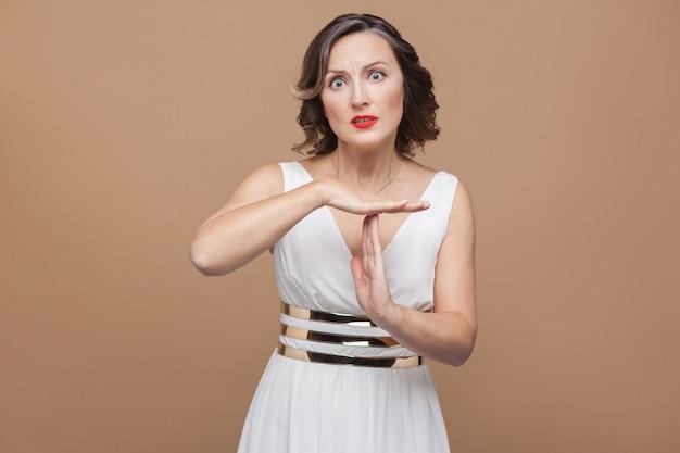 タイムアウトサインジェスチャーを示す疲れた中年の実業家。白いドレス、赤い唇、暗い巻き毛の髪型で感情的に表現する女性。スタジオショット、屋内、ベージュまたは茶色の背景に分離