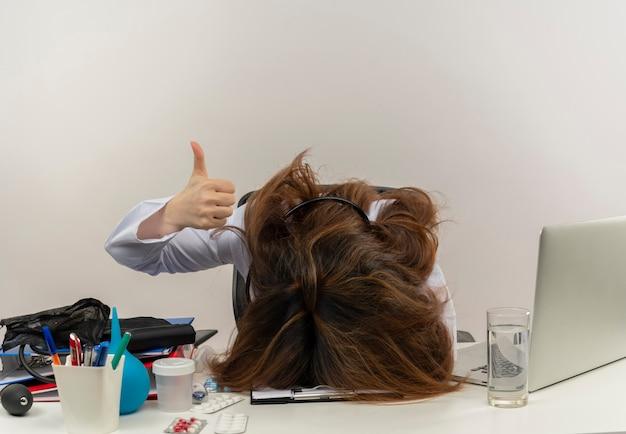 Medico femminile di mezza età stanco che indossa veste medica e stetoscopio seduto alla scrivania con appunti di strumenti medici e laptop mettendo la testa sulla scrivania che mostra il pollice in alto isolato