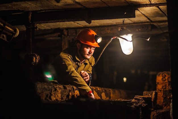 A tired miner in a coal mine looks at the light. work in a coal mine.