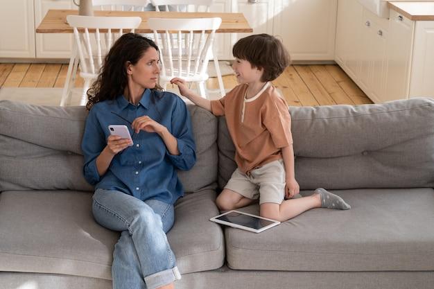 피곤한 엄마는 아들이 나쁜 행동을 하고 소파에 앉아 일한 후 스마트폰으로 인터넷 서핑을 하려고 합니다