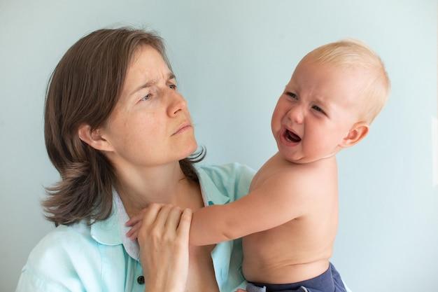 피곤한 엄마는 우는 아기를 손으로 진정시키려고 합니다. 신생아 울화통. 모성 개념입니다. 집에 아이가 있는 우울한 여자.