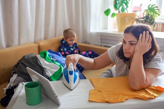 Усталая мама смотрит видео на планшете и гладит вещи рядом с сыном тоже на смартфоне