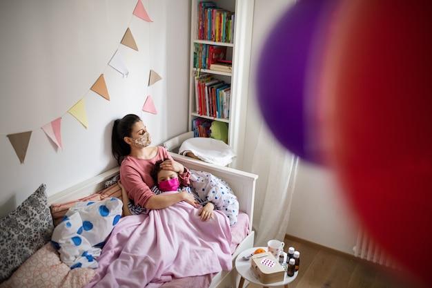 家のベッドで寝ている病気の小さな娘の世話をしている疲れた母親、コロナウイルスの概念。