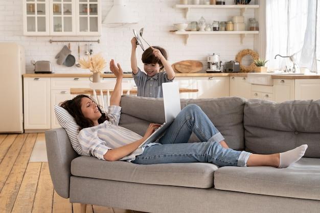 피곤한 어머니는 활동적인 시끄러운 아이와 함께 소파에 있는 노트북에서 업무 유형의 비즈니스 이메일에 집중하려고 합니다.