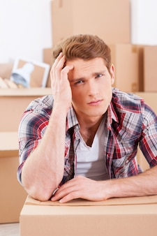 Tired of moving. depressed young man sitting on the floor and holding hand in hair while cardboard boxes laying on the background