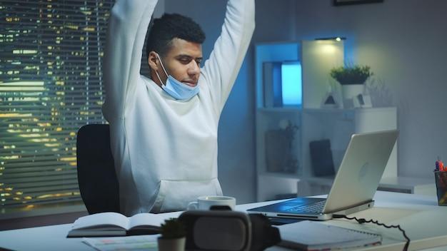 防護マスクと夜遅くまで家で仕事をしてウォーミングアップ活動をして疲れている多民族の男