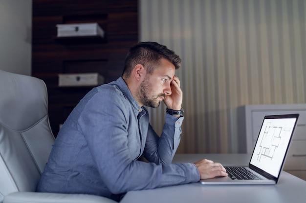Утомленный нервный архитектор работая над большим проектом пока сидящ в офисе поздно ночью.
