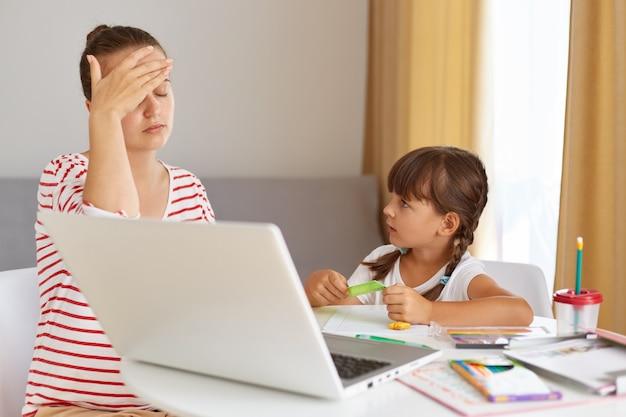 ストライプのカジュアルシャツを着て疲れている神経質な女性は、家事を説明するのに疲れている、疲れている、手のひらで目を覆っている、子供が母親を見ている、オンライン教育。