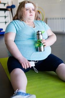 マットの上に座って疲れた肥満女性