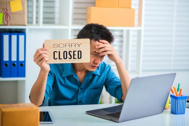 不幸を感じているビジネスマンにうんざりしていて、閉じた看板を持っているストレス。
