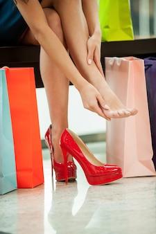 Устали от дневных покупок. обрезанное изображение молодой женщины, отдыхающей и массирующей пальцы ног с сумками для покупок рядом с ней