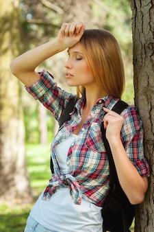 하이킹에 지쳤습니다. 배낭을 메고 나무에 기대어 눈을 감고 있는 피곤한 젊은 여성의 측면