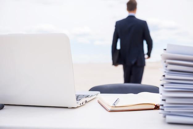 사무실 생활에 지쳤습니다. 그의 작업 장소에서 걸어가는 formalwear에서 남자의 후면보기