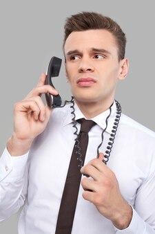 사무실 작업에 지쳤습니다. 셔츠와 넥타이에 우울한 젊은이 회색 배경에 서있는 동안 전화로 얘기하고 전화선을 잡고