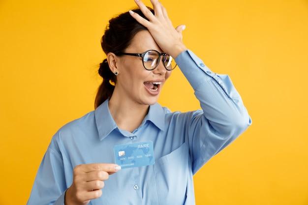Устали от продажи. дама в очках держит кредитную карту и положила руку ей на голову.
