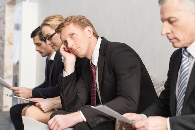 Устал ждать. скучно молодой человек в строгой одежде, держа голову за руки и глядя в сторону, сидя в ряду с другими людьми