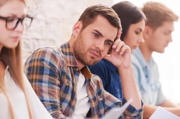 Устал ждать. обеспокоенный молодой человек держит голову в руке и смотрит в сторону, сидя в ряд с другими людьми