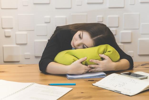 베개에 사무실에서 자 고 피곤된 사무실 여성. 힘든 일, 일보다