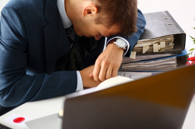 Tired office male clerk in suit take nap on table workplace full of exam papers. sleepy white collar career frustration freelance employment fail study problem low energy down