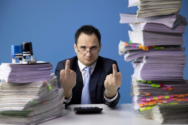 Tired office worker doing middle finger sign, sitting at desk with huge pile of documents