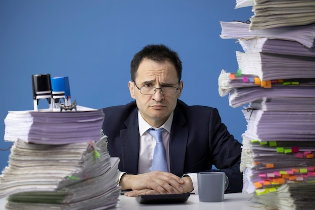 Tired office worker grimacing, surrounded by documents