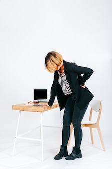 Tired office worker having spine problem