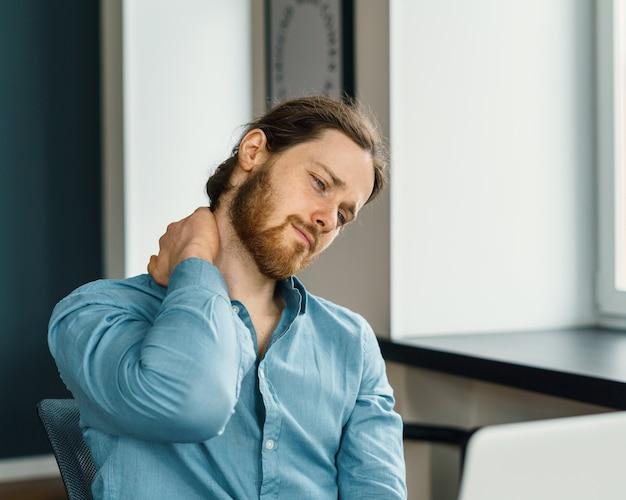 Усталый офисный работник страдает от боли в шее в офисе