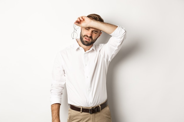 Tired office worker take-off glasses, wiping sweat off forehead with his arm, standing drained against white background.