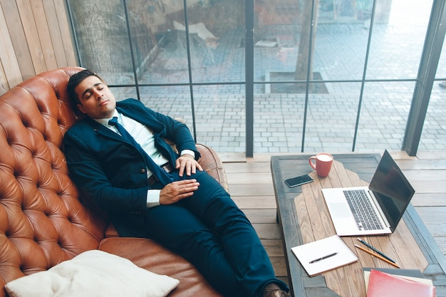 Tired office worker with eyes closed lying on leather sofa.