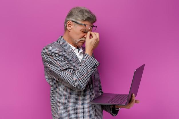 Vecchio stanco che tiene il computer portatile mentre rimane sul muro viola