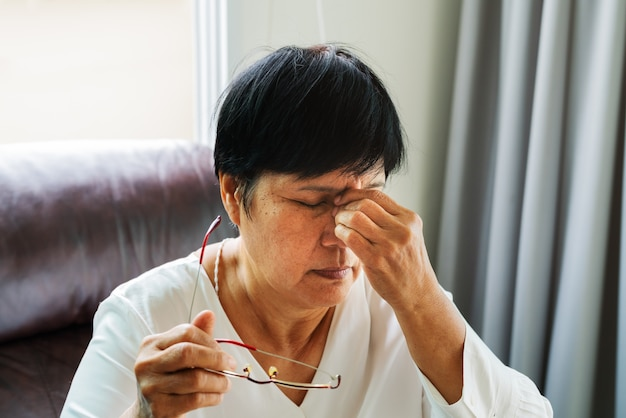 Tired old woman removing eyeglasses massage eyes after reading book