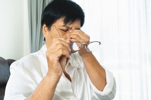 피곤한 할머니는 안경을 벗고 종이책을 읽은 후 눈을 마사지합니다. 장시간 안경으로 인한 불편감, 눈의 통증 또는 두통으로 고통받는