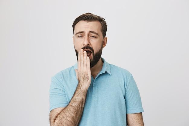 Усталый или скучающий бородатый мужчина зевает, выглядит неохотно
