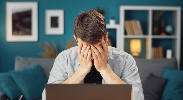 居間のコンピューターの前に座っている手で顔を閉じる疲れているまたは疲れた男
