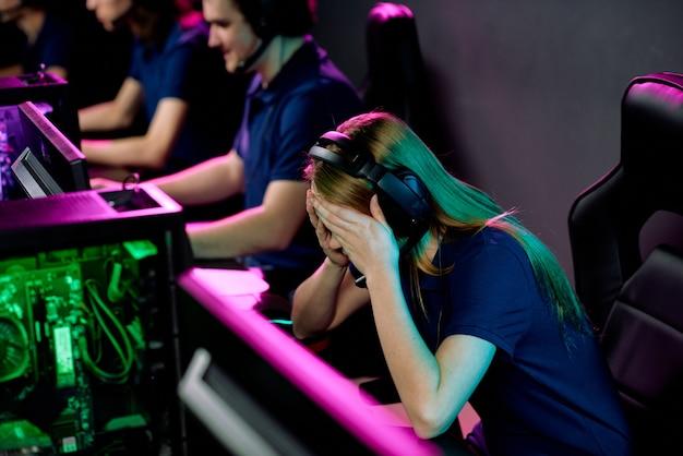 コンピューターのモニターの前で机の上に曲がっているときに頭に触れているヘッドセットの疲れているまたは失敗した女の子