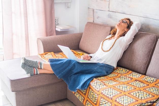 Усталая или полная мыслей кавказская одинокая женщина работает дома с современным ноутбуком, окрашенным ключевыми словами, такими как путь художника и образ жизни. лягте на диван и посмотрите вверх, чтобы найти решение