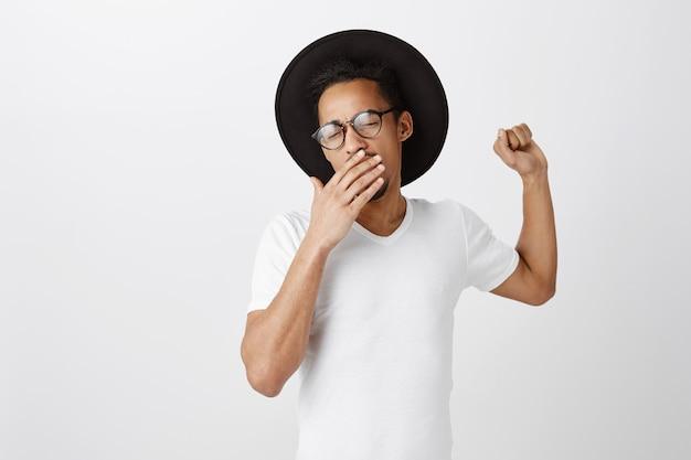 疲れたまたは眠そうなアフリカ系アメリカ人の男性がカジュアルなtシャツのあくびをし、カバーを開けて手で口を開いた 無料写真