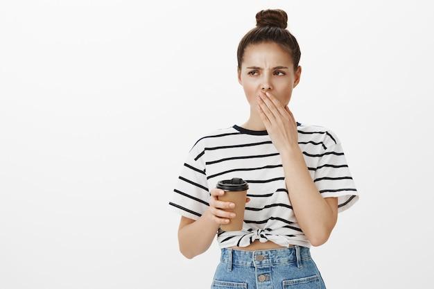 コーヒーを飲みながらあくびをして疲れているか眠いかわいい若い女性は、エネルギーを必要としています