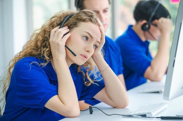 Уставший или утомленный персонал колл-центра перед экраном компьютера с телефонной гарнитурой с признаками сильной головной боли.