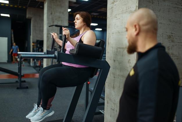 スポーツ クラブのトレーナーと疲れた太りすぎの女の子、インストラクターとのフィットネス トレーニング。太りすぎ、肥満に対する有酸素運動、ジムに悩む女性