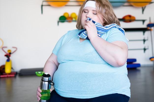 ジムで疲れている太りすぎの女性