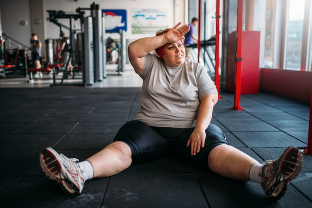 疲れた太りすぎの女性がジムの床に座っています。カロリー燃焼、スポーツクラブの肥満女性、太った人