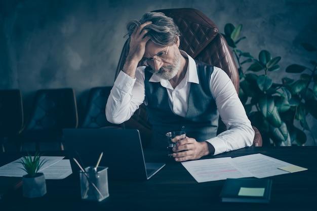 Усталый перегруженный работой бизнесмен, имеющий головную боль, держит лекарства в стекле
