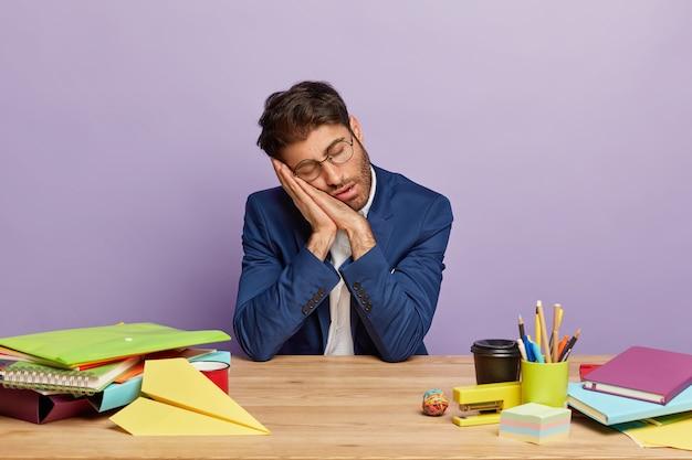 Усталый перегруженный работой бизнесмен, сидя за офисным столом