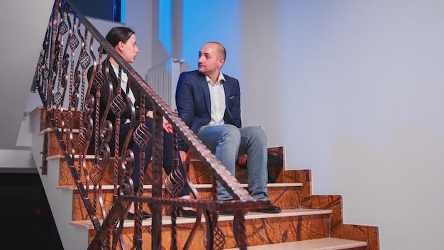 企業の営業所の階段に座って話し合って休憩している疲れた過労のビジネスマン。深夜に一緒に残業をしている同僚の起業家が締め切りプロジェクトの計画を立てる